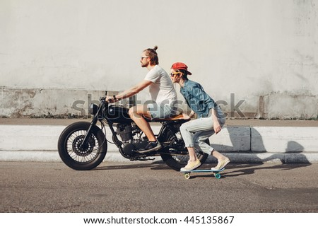 Group of friends skating and cycling in an urban area - Cheerful teenagers having fun outdoors. Young man and woman riding on a sunny day. - stock photo