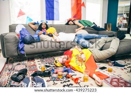 Group of friends sleeping in a living room after party - Drunk supporters resting after celebrating their teams at a sport event - stock photo