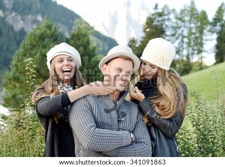 Group of friends smiling and joking in a beautiful autumn day inside a mountain resort. Two women tease their friend outside in the nature with autumn or winter clothes - stock photo