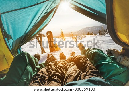 Group of friends snowboarders and skiers relaxing in tent on background of sunset and mountains valley. Sheregesh resort, Siberia, Russia - stock photo