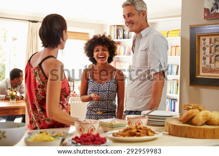 Group of friends stand talking at a dinner party - stock photo