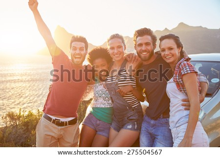 Group Of Friends Standing By Car On Coastal Road At Sunset - stock photo