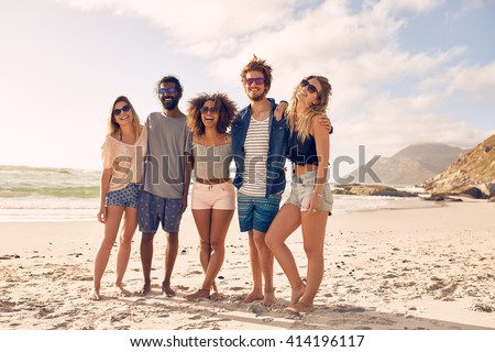 Group of friends standing together at a beach on a summer day.  Happy young people enjoying a day at beach. - stock photo