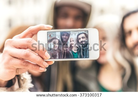 Group of friends taking a selfie - Multi-ethnic group of people having fun with modern technology - stock photo