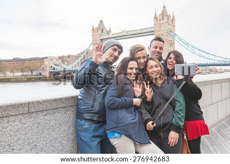 Group of friends taking a selfie using a selfie stick in London with Tower Bridge on background. They are four girls and two boys in their twenties, embracing and having fun together. - stock photo