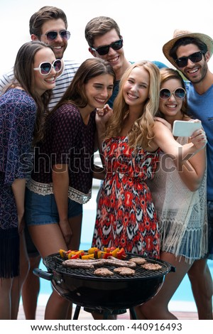 Group of friends taking a selfie while preparing barbecue near pool - stock photo