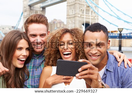 Group Of Friends Taking Selfie By Tower Bridge In London - stock photo