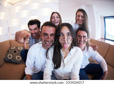 group of friends taking selfie photo with tablet at modern home indoors - stock photo