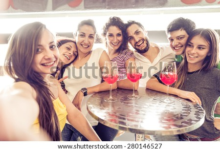 Group of friends taking selfie with smartphone in a lounge bar - People celebrating in a club, looking at camera and having some cocktails - stock photo
