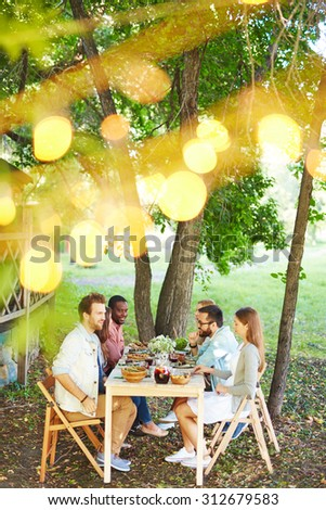 Group of friends talking by Thanksgiving dinner outdoors - stock photo