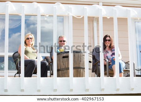 Group of friends talking on home patio - stock photo