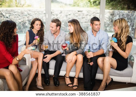 Group of friends talking to each other and cocktail drinks at party - stock photo