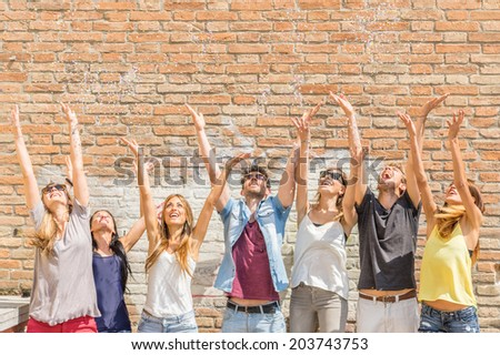 Group of friends throwing confetti in the air - happiness,sale,friendship,summer concept - stock photo