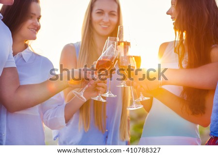 Group of friends toasting champagne sparkling wine at a relax party celebration gathering at the beach - stock photo