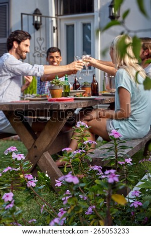 Group of friends toasting to celebration with wine drinks at garden outdoors party - stock photo