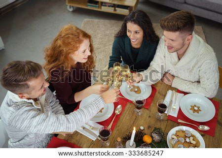group of friends toasting with champagne while having christmas dinner - stock photo