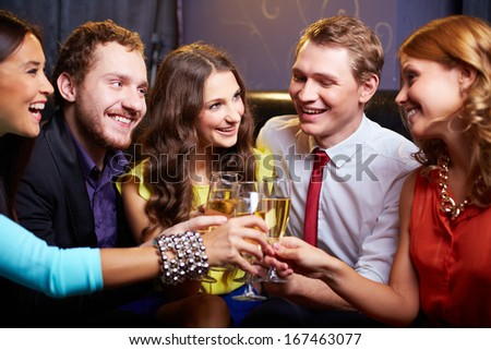 Group of friends toasting with flutes of champagne at party - stock photo