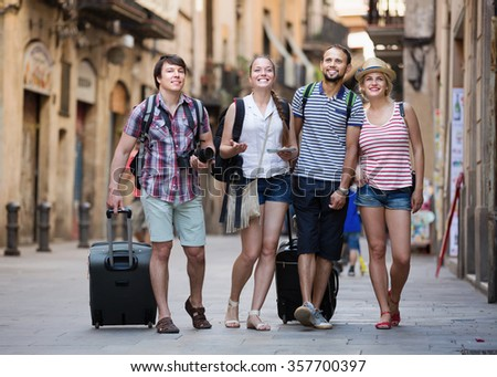 Group of friends together at vacation walking at the street - stock photo