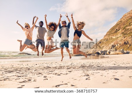 Group of friends together on the beach having fun. Happy young people jumping on the beach. Group of friends enjoying summer vacation on a beach. - stock photo