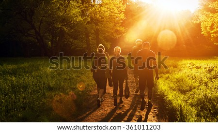 Group of friends walking with backpacks in sunset from back. Adventure, travel, tourism, hike and people friendship concept. Sports activity - stock photo