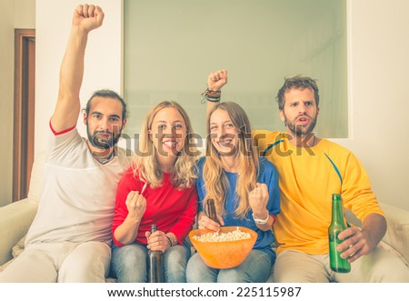 group of friends watching sport match in front the television. they are happy about the score - stock photo