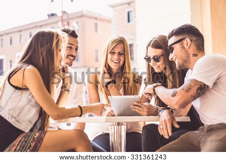 Group of friends watching tablet in a bar. Sitting in a bar in the city center and Meeting friends. - stock photo