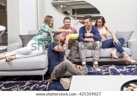 group of friends watching tv and eating popcorn on sofa - stock photo