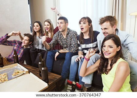 Group of friends watching TV match and cheering - stock photo