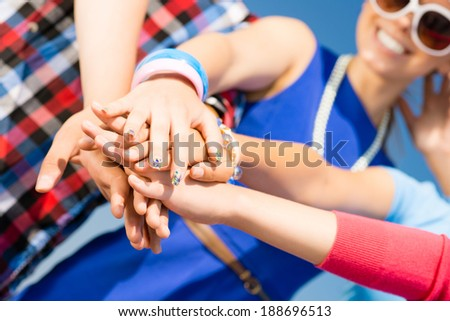 group of friends with arms folded in a column, teamwork - stock photo