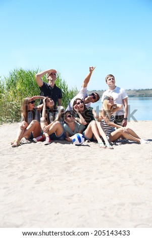 Group of friends with ball at beach - stock photo