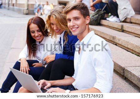 Group of friends with laptop sitting on a steps outdoors  - stock photo