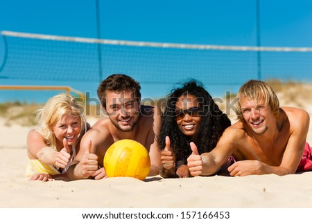 Group of friends - women and men - playing beach volleyball, they having a break and lying in the sun - stock photo