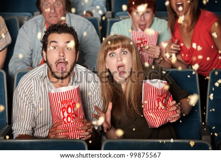 Group of frightened people watching movie spill popcorn - stock photo