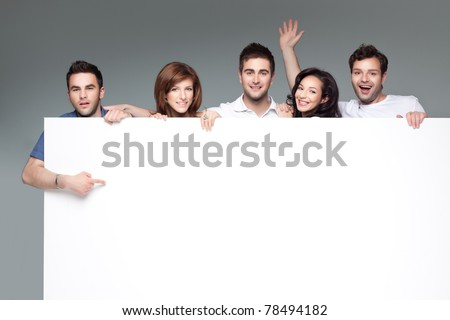 group of funny friends holding a blank banner - stock photo