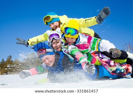 group of funny friends slide downhill together on mountain holiday - stock photo