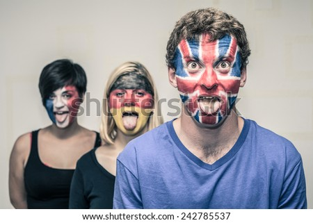 Group of funny people with painted European flags on their faces and sticking out tongue. - stock photo