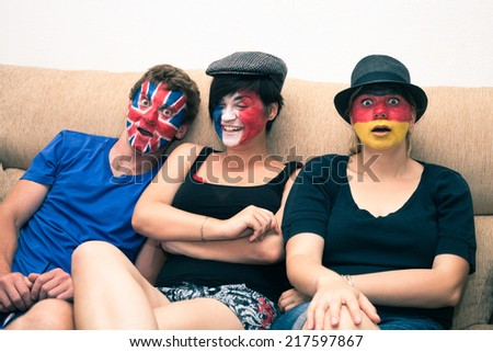 Group of funny people with painted flags on their faces and sitting on sofa. - stock photo
