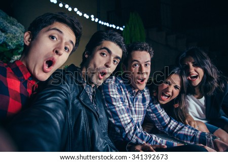 Group of funny young friends shouting while taking a selfie photo in a outdoors party. Friendship and celebrations concept. - stock photo