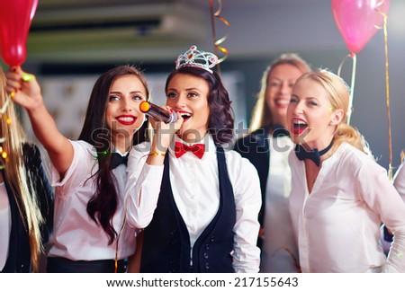 group of girls friends having fun on karaoke party - stock photo