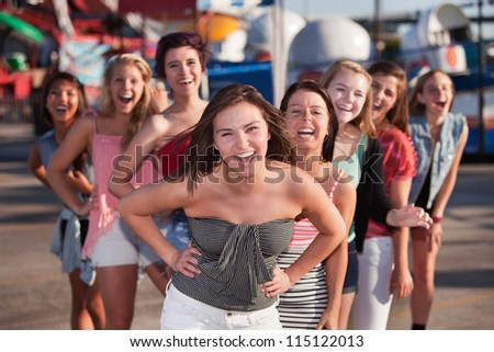 Group of 8 girls laughing together at a theme park - stock photo