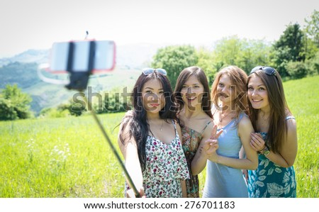 group of girls making selfie with selfie stick. concept about friendship,nature,technology, and people - stock photo