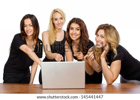 Group of girls pointing at a laptop with white background - stock photo