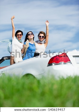 Group of girls stands in the cabriolet with hands up. Happy journey of joyful teenagers - stock photo