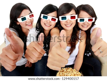 Group of girls watching movie showing thumbs up - stock photo