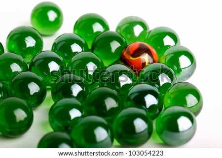 Group of green glass marbles with one orange marble in a concept of uniqueness or individuality	 - stock photo
