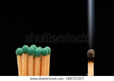 Group of green wooden matches standing with burnt smoked match, isolated on black background - stock photo