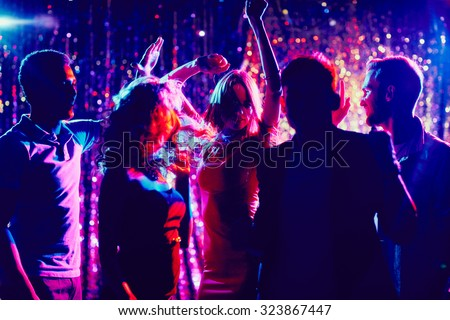 Group of guys and girls dancing in the night club - stock photo