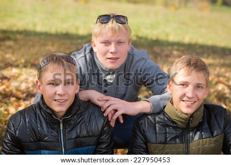 Group of guys in the autumn park, two of the boys twin brothers. Image with Instagram-like filter - stock photo
