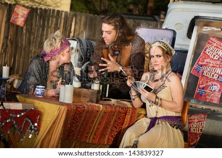 Group of gypsies outside meeting at fortune teller stand - stock photo