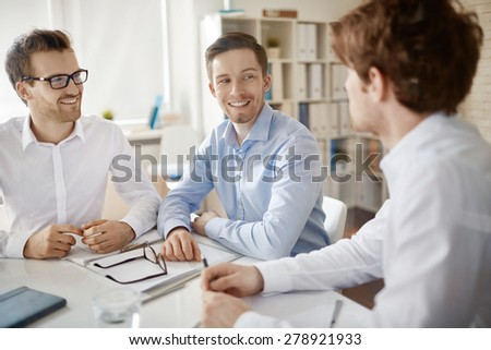 Group of handsome employees discussing plans in office - stock photo